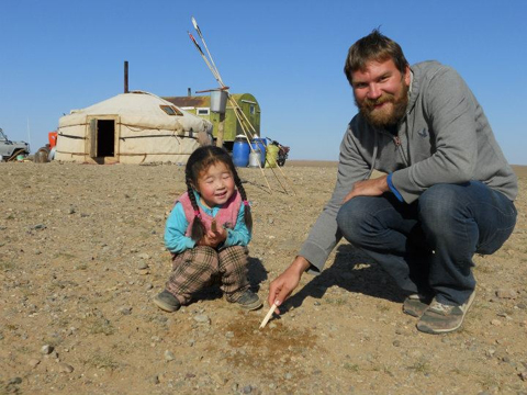 Peter Berg visiting with a young friend in the Gobi Desert of Mongolia. Thunderbird Atlatl darts are in the background near the yurt or ger.