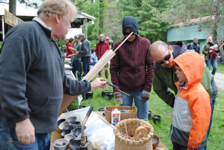 Bob Berg shows a primitive flint tool to a family at Primitive Pursuits Day in Ithaca, New York