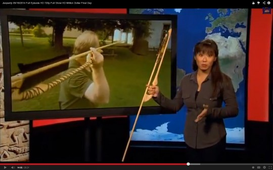 Screenshot of the Atlatl Clue. The presenter is holding our Catatonk Atlatl and a Dart. In the video clue, Bob is casting a dart with our Wyalusing Atlatl
